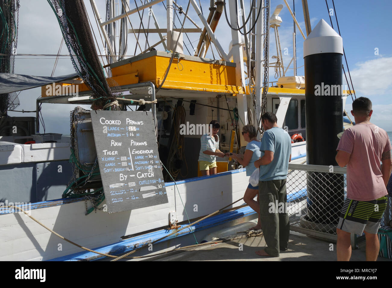 People buying prawns from trawler at wharf, Port Douglas, Queensland, Australia. No MR or PR - Stock Image