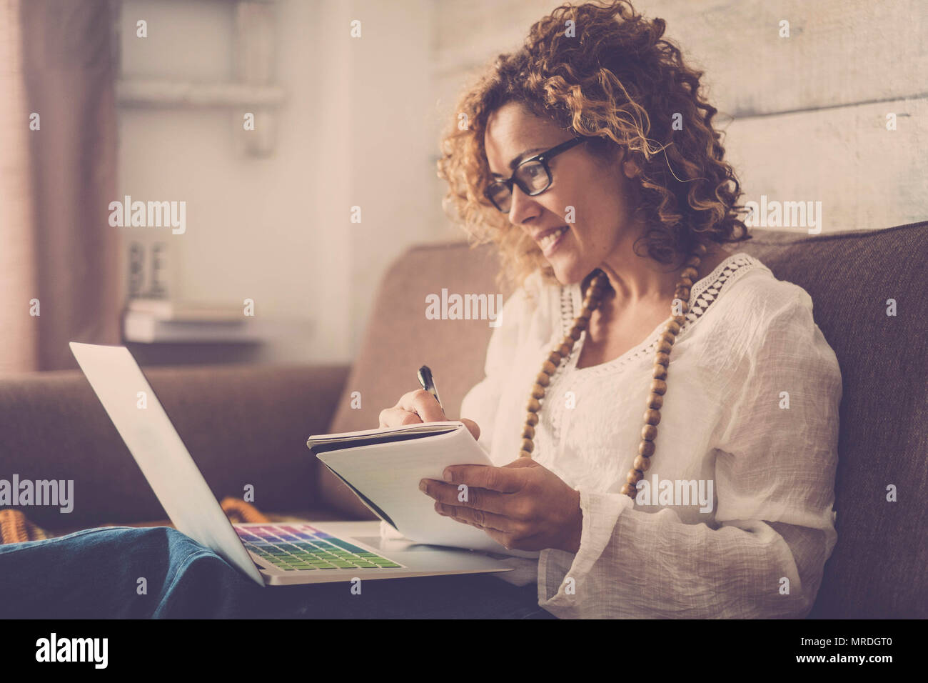 beautiful woman smile and write notes on paper working on a laptop freedom from office at home. alternative lifestyle and place to work on. vintage re - Stock Image