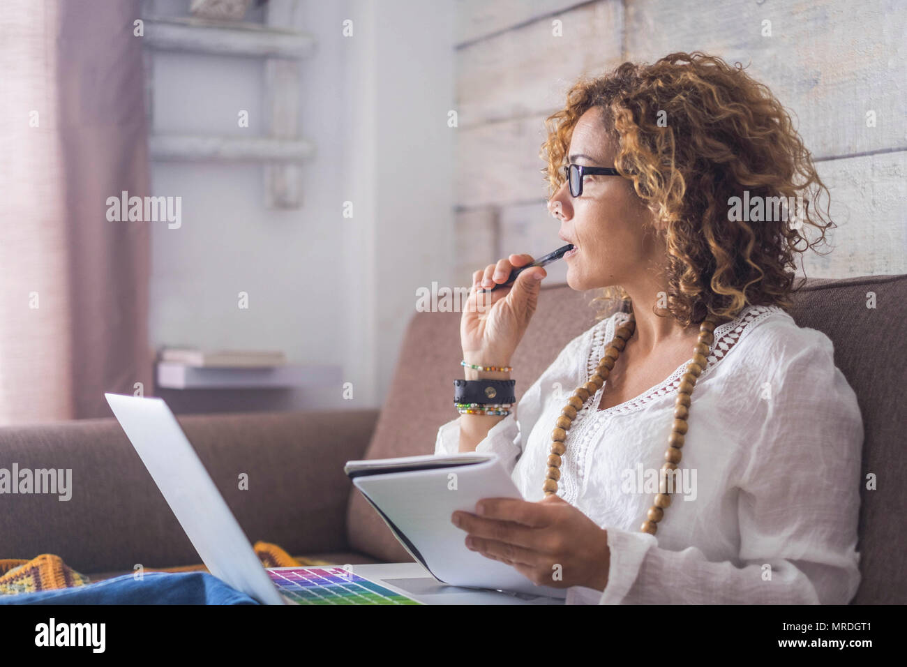 beautiful woman think and write notes on paper working on a laptop freedom from office at home. alternative lifestyle and place to work on. Nice life  - Stock Image
