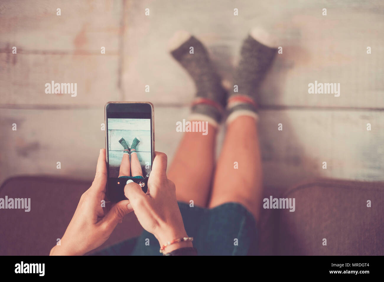 beautiful caucasian woman take picture with mobile phone at her legs against the wall with nice and funny socks. home alternative lifestyle and indepe - Stock Image