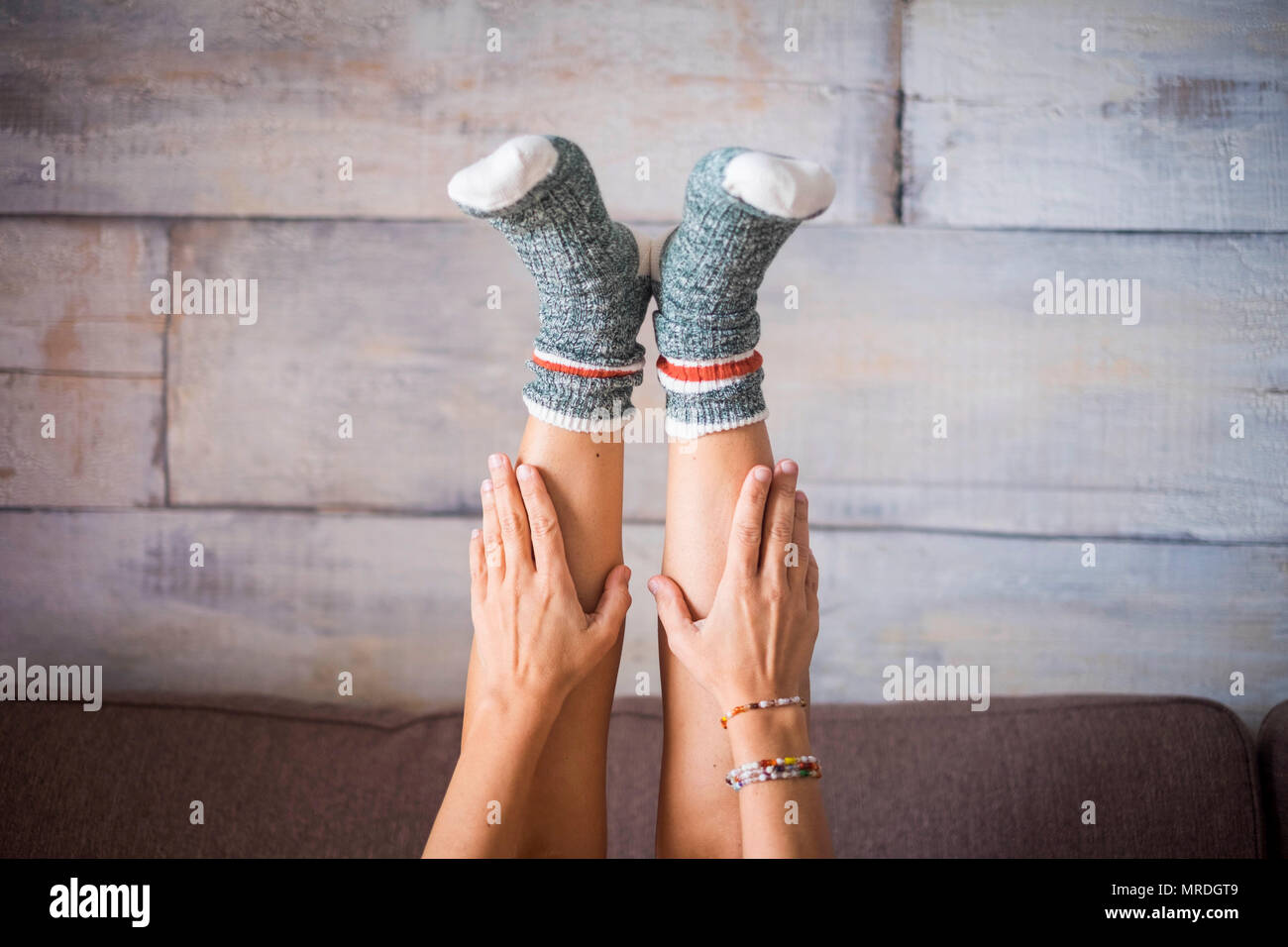 in the middle composition with beautiful woman legs downside with funny and colored socks taken by hands. alternative joy and lifestyle concept for in - Stock Image