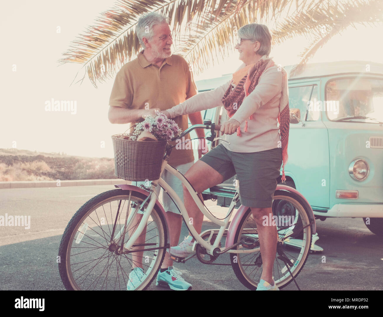 man and woman caucasian mature have fun outside with old bike and vintage van. vacation and happy retired concept. backlight from sun for nice models  - Stock Image