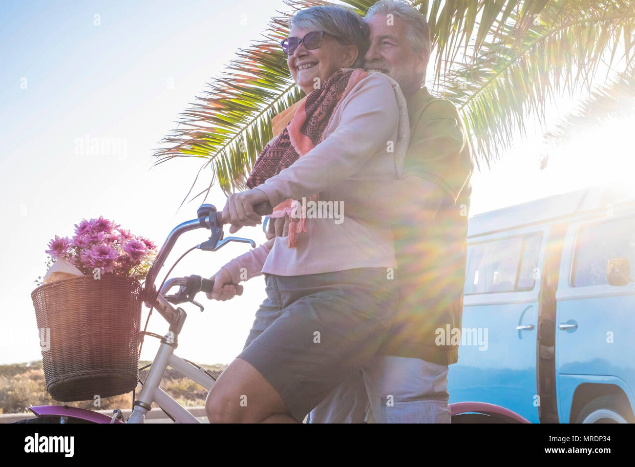 nice beautiful couple of seniors grandfathers going together on a bicycle outdoor in a tropical place. old vintage blue van in the background. happine - Stock Image