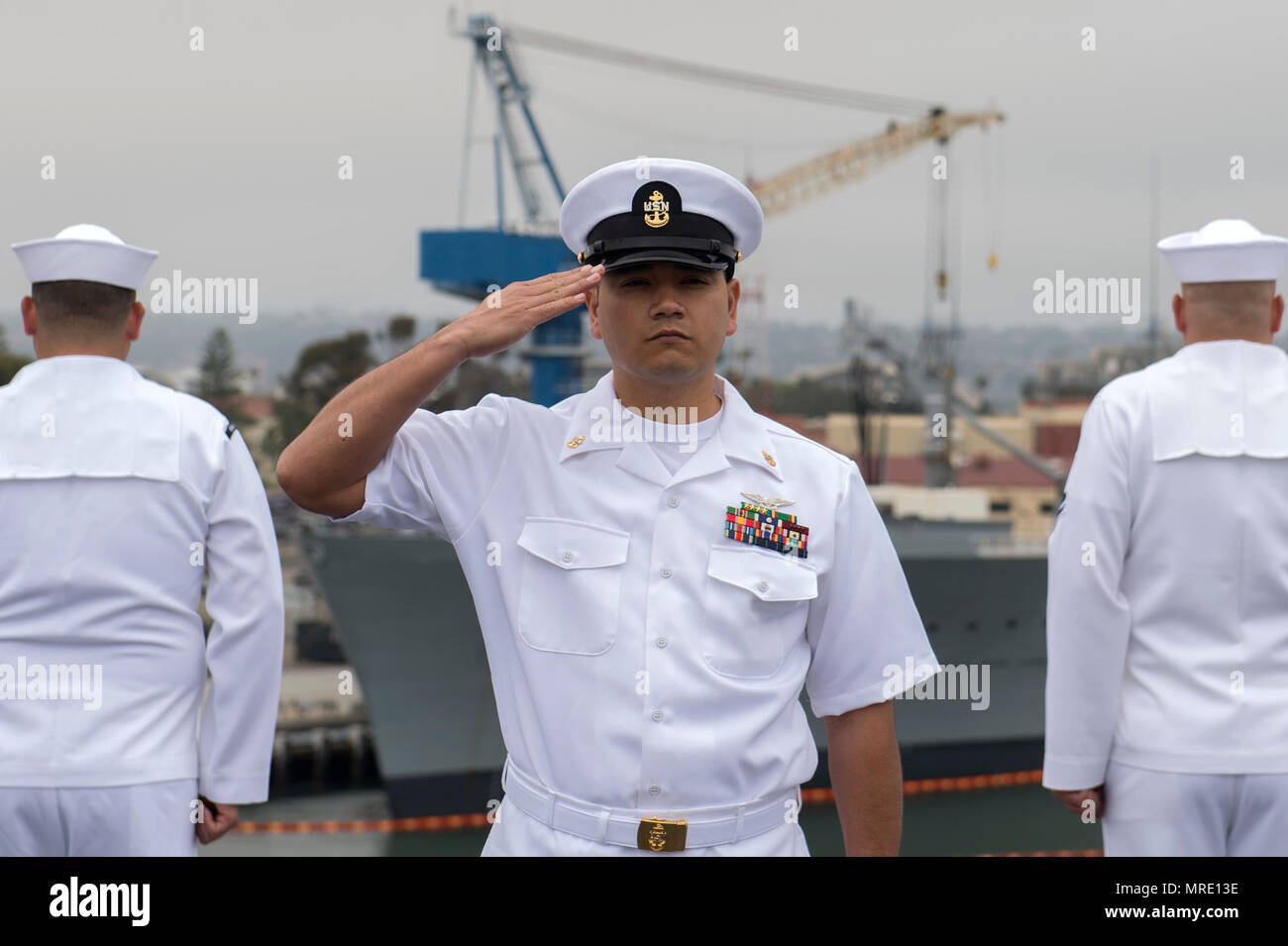 SAN DIEGO (June 5, 2017)  Chief Aviation Machinist's Mate Rodrigo Zurita renders honors to the USS Midway (CV 41) Aircraft Carrier Museum as the aircraft carrier USS Nimitz (CVN 68) passes on the 75th anniversary of the Battle of Midway, June 5, 2017, in San Diego. Nimitz is joining Carrier Air Wing 11, Destroyer Squadron 9 and the rest of Carrier Strike Group 11 to depart on a regularly scheduled deployment. (U.S. Navy photo by Mass Communication Specialist 2nd Class Elesia K. Patten) - Stock Image