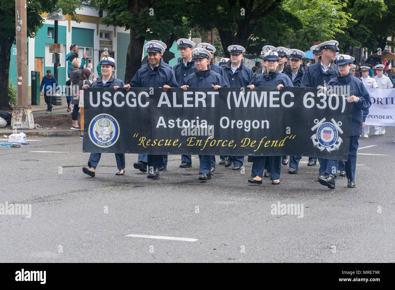 170610-N-ZP059-107 PORTLAND Ore., (June 10, 2017) – U.S Coast Guard members assigned to the medium endurance cutter Alert (WMEC-630) walk along the Rose Festival Parade route in Portland, Ore., during Portland Rose Festival Fleet Week. The festival and Portland Fleet Week are a celebration of the sea services with Sailors, Marines, and Coast Guard members from the U.S. and Canada making the city a port of call. (U.S. Navy photo by Mass Communication Specialist 2nd Class Jacob G. Sisco/Released) Stock Photo