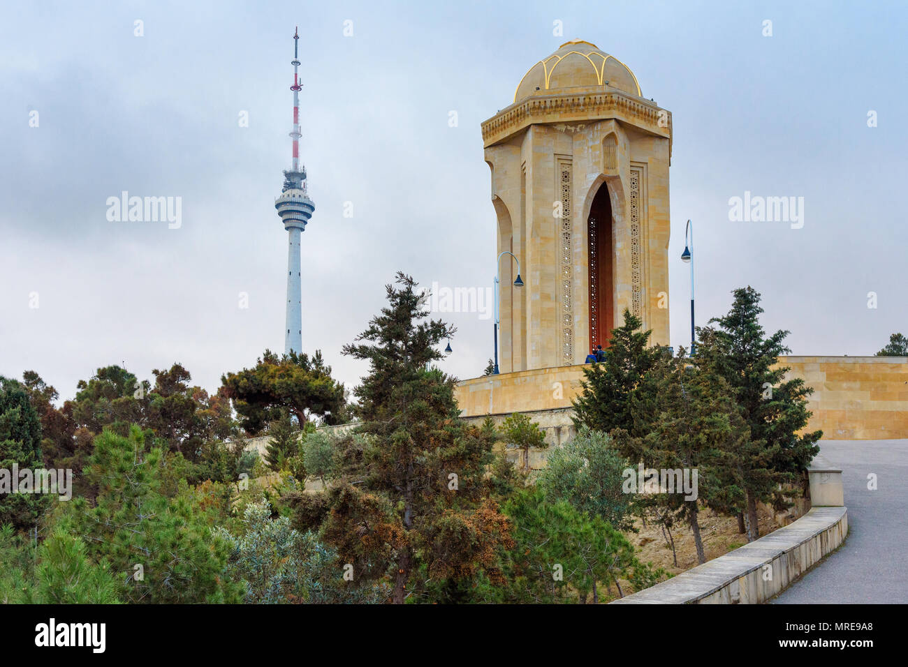 Baku, Azerbaijan - March 11, 2018: Shahidlar Monument or Eternal flame Monument on Martyrs' Lane. And Tv tower in the evening Stock Photo