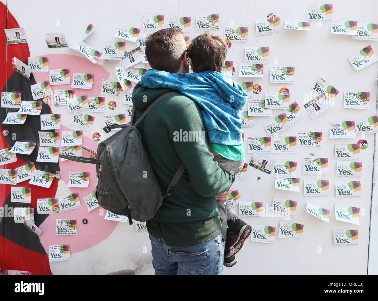 A father and son look at sympathy messages left at a mural