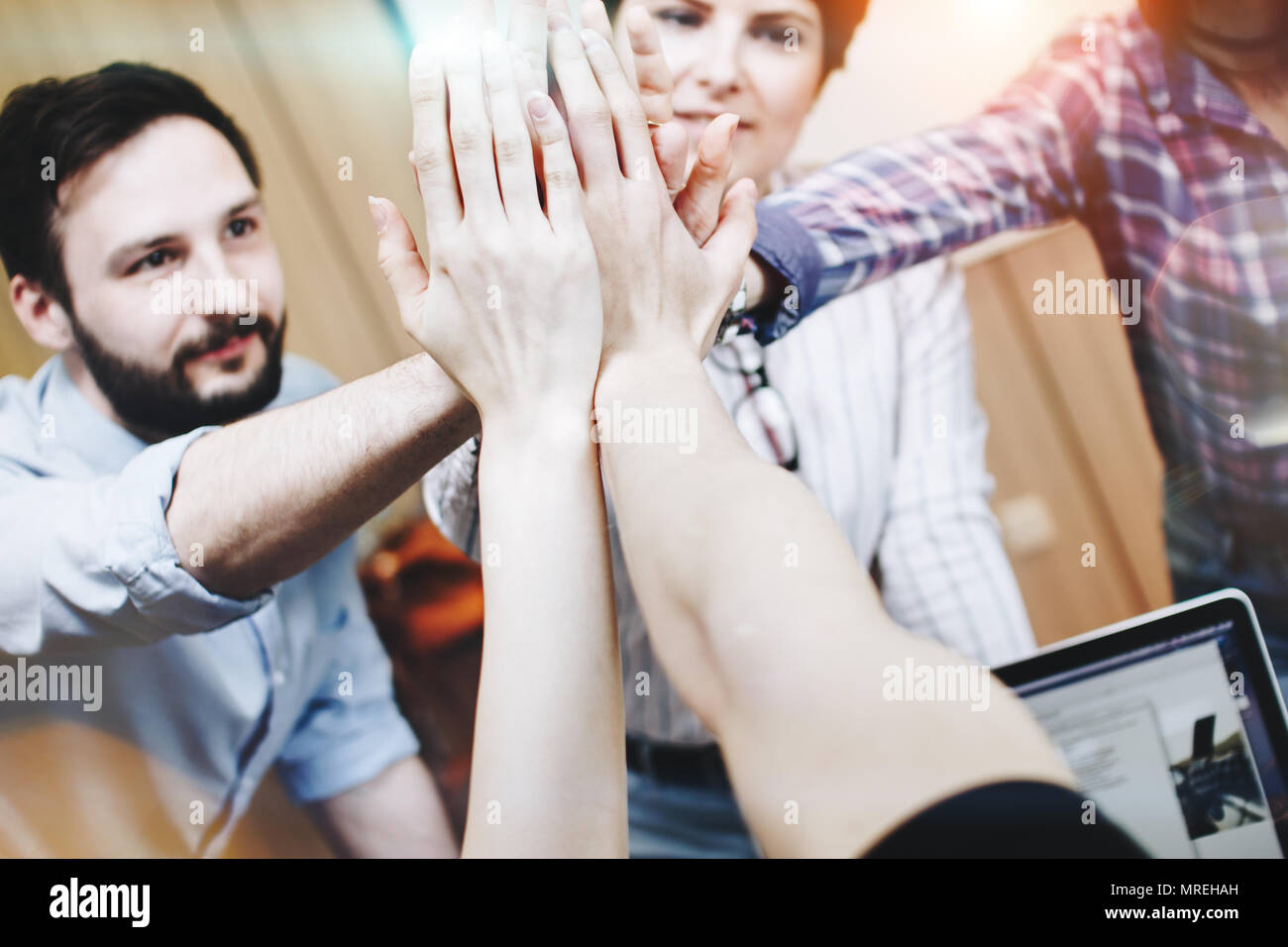 Close-knit team of young people achieved success in their work. Modern businessmen have developed a successful plan - Stock Image