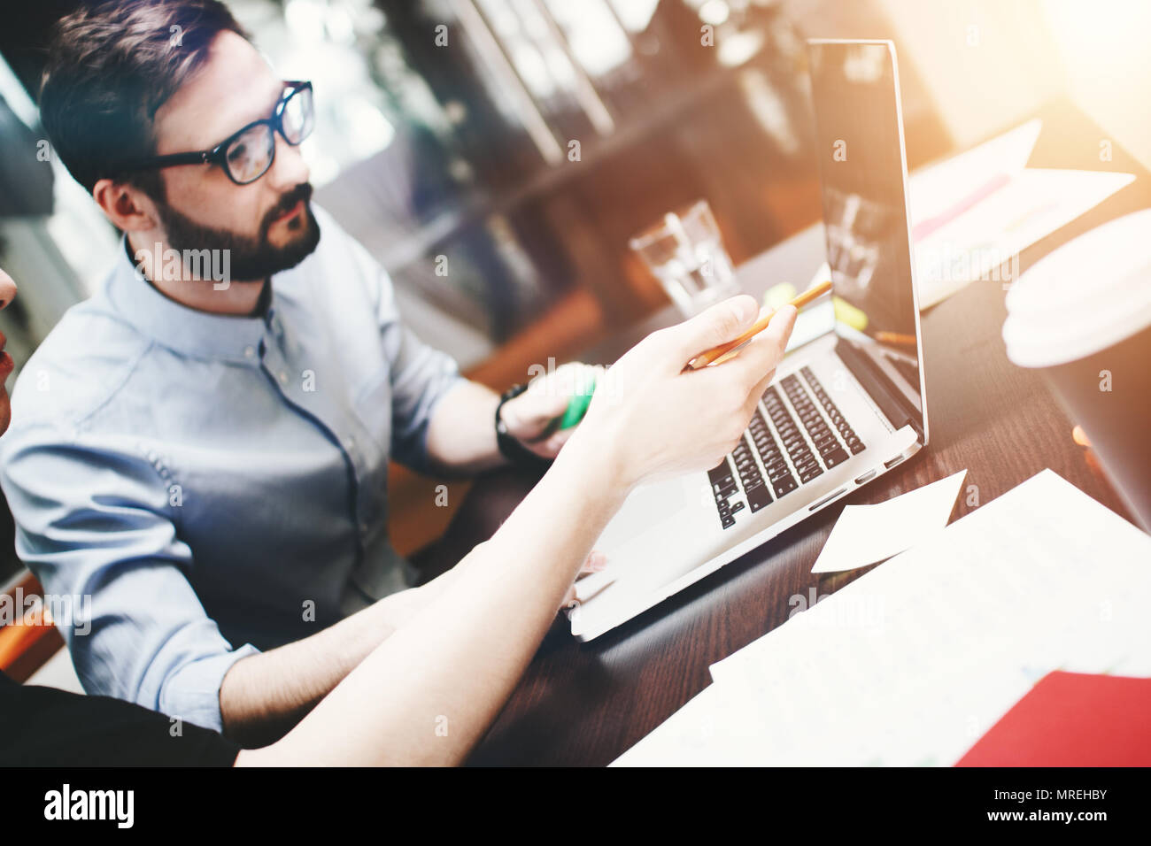 Young bearded businessman in glasses analyzes the teamwork done. Works at the desk with a laptop and office accessories. Blurred background - Stock Image