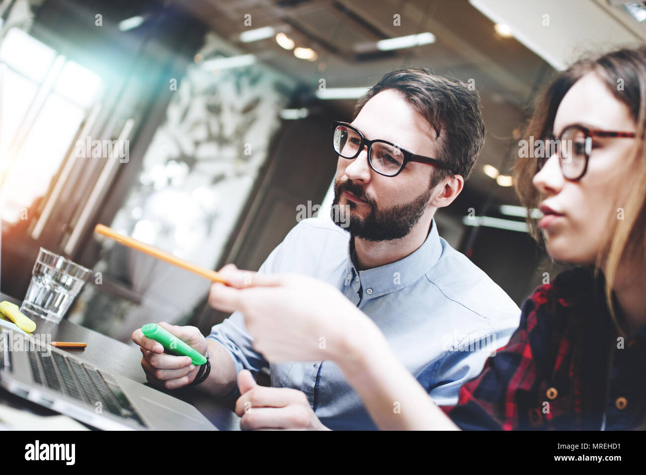 Team of businessman working on a new concept behind a modern laptop in open space office. Blurred background. Brainstorming a new startup - Stock Image