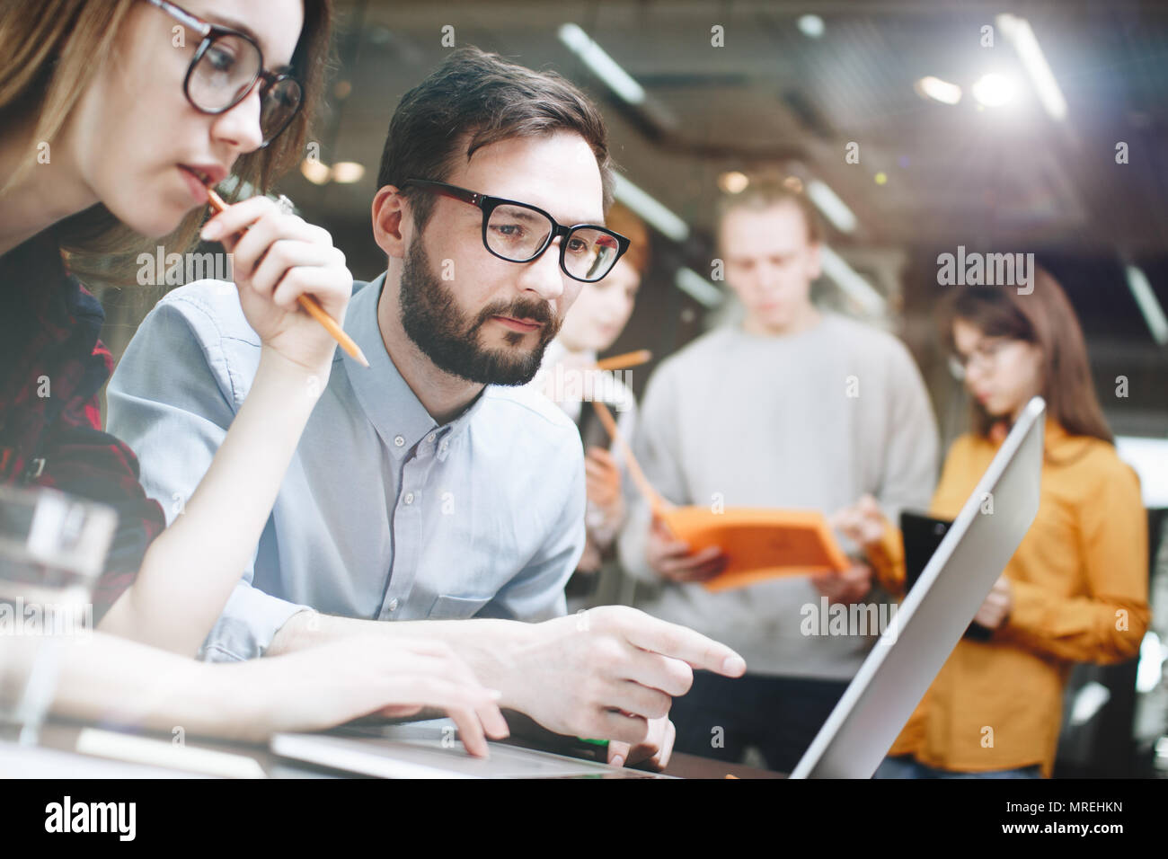 Business team working on a new project on a laptop. Discussion of a new work plan. A woman with glasses and a bearded man discussing a startup plan - Stock Image