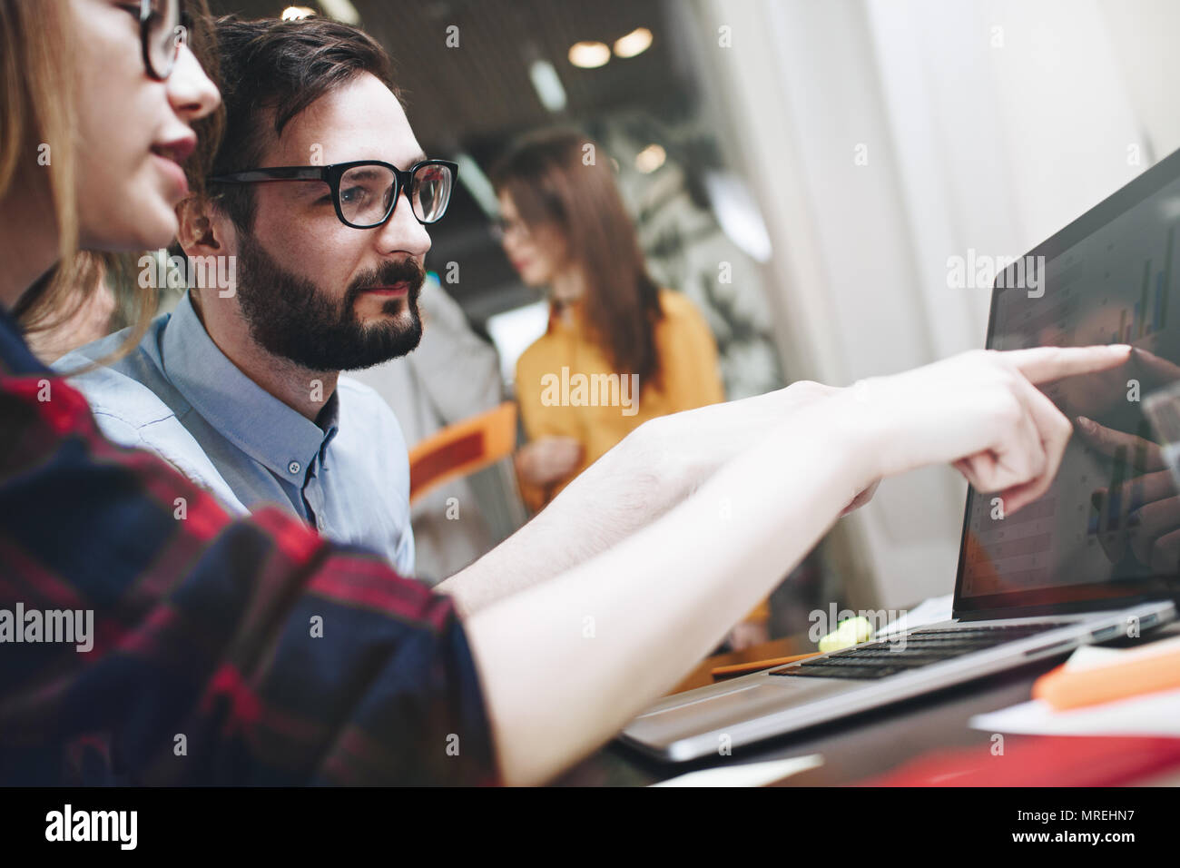 Bearded man and woman discussing marketing plan. Product meeting. Startup in open space office - Stock Image