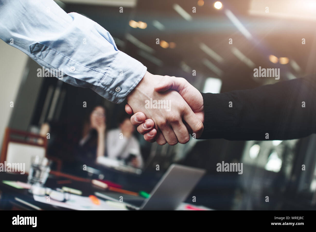 Two men handshakes after important business conference in modern loft room - Stock Image