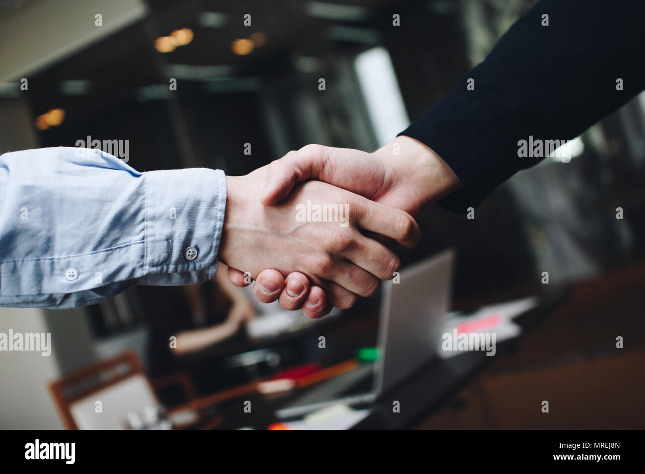 Two managers in casual clothing in meeting room handshakes after finding compromise - Stock Image