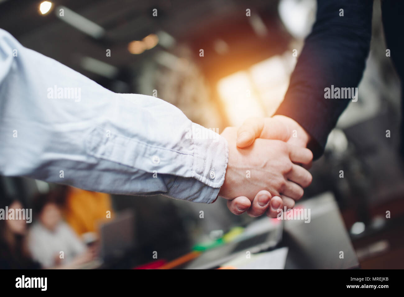 Group of engineers shake hands after successfully solving issues. Lens flare effect. - Stock Image