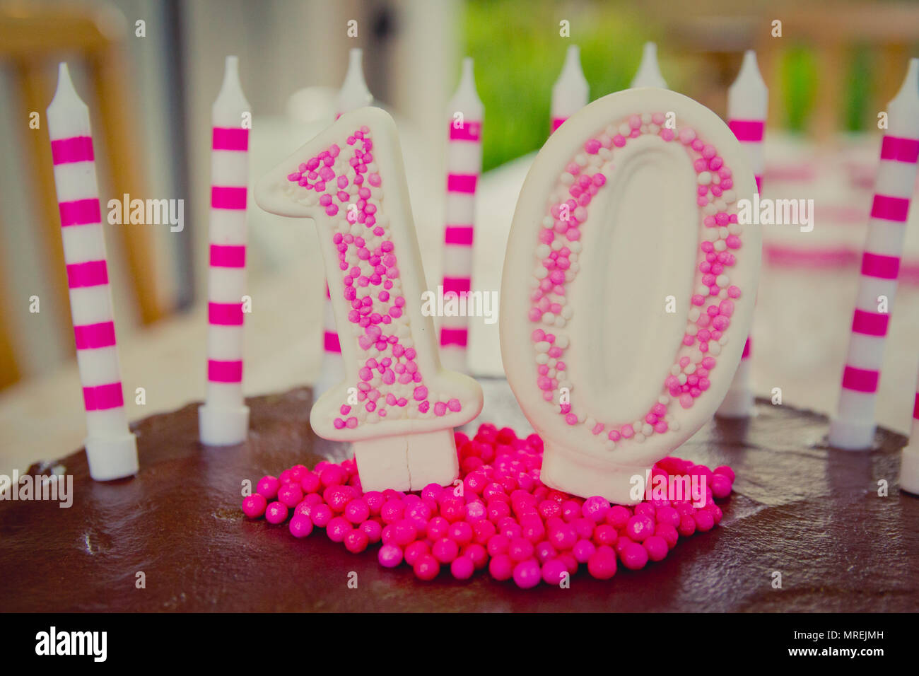 Cake decoration in the figure of the number 10, made of sugar dough and candy in white and pink. The decoration placed on brown chocolate cake. There  - Stock Image