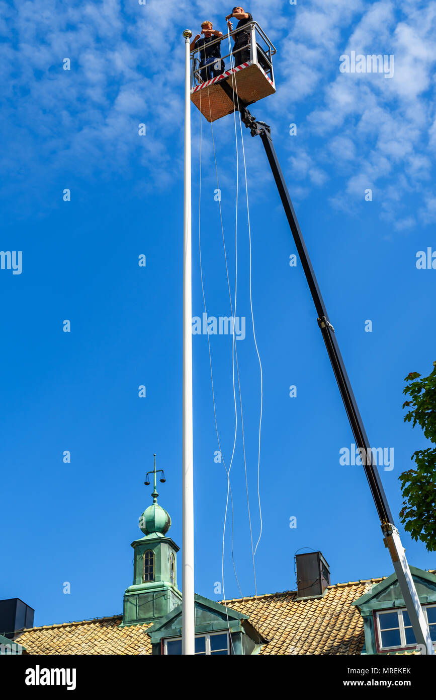 Angelholm, Sweden - May 15, 2018: Travel documentary of everyday life and place. Two persons in a boom lift putting rope on a tall flagpole outside th - Stock Image