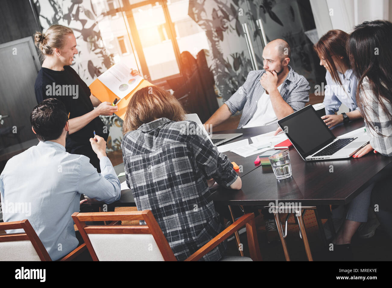 Six people working in loft space. Coworking startup meeting. Teamwork and brainstorming. Intentional little lens flares - Stock Image