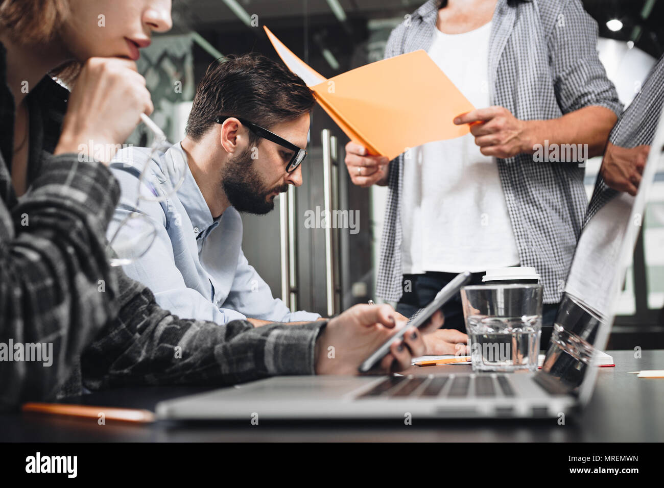 Team of friends or partners holds a business meeting in loft office. Business crew working with startup studio. Using digital tablet and gadgets - Stock Image