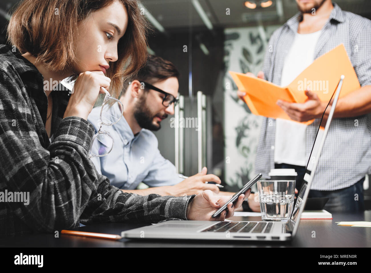 Team of modern startup managers works on laptop in loft space. Teamwork brainstorming concept. Analyzing new idea and developing plan - Stock Image