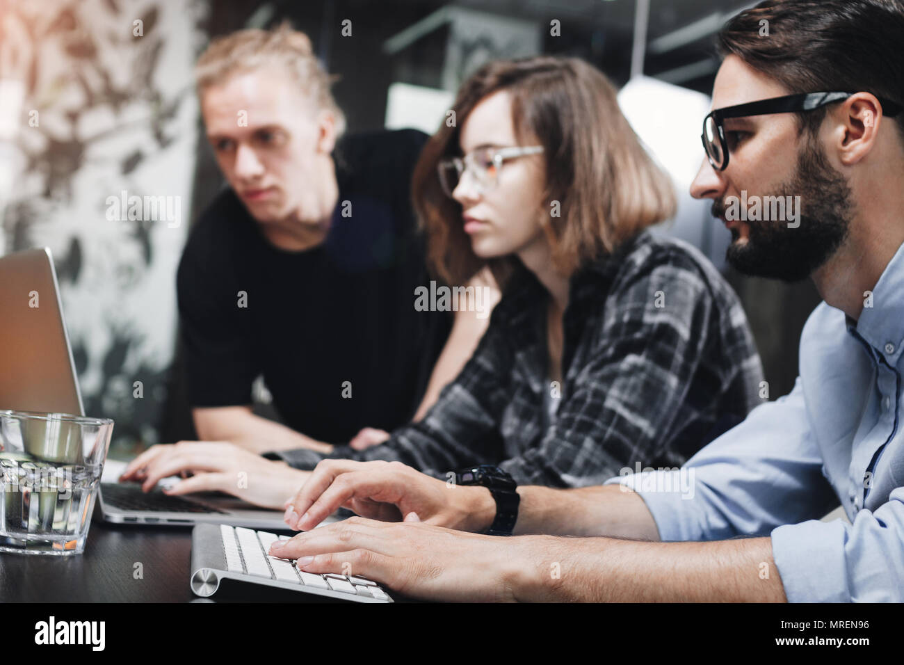 Account managers young crew works with new startup in modern loft space. Team brainstorming. Photo of creative managers crew working on new project in - Stock Image
