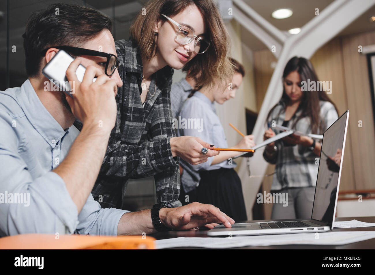 Teamwork concept. Coworking people work together in loft office. Bearded businessman talks on smartphone. Female manager holding presentation on lapto - Stock Image