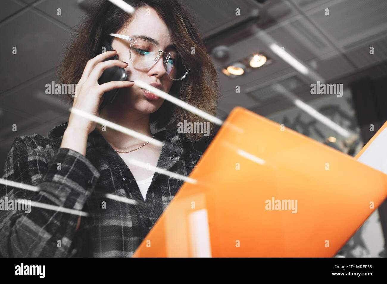 Young pensive business woman in glasses talking something on phone with manager. Photo of close-up female speaking on smartphone in modern office Stock Photo