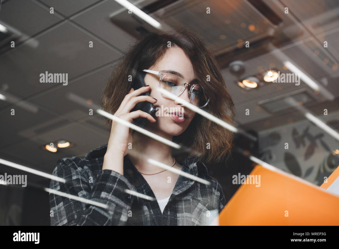 Close-up photo of woman talking on phone with director of development in evening office and holding folder with documents. Blurred background, little  - Stock Image