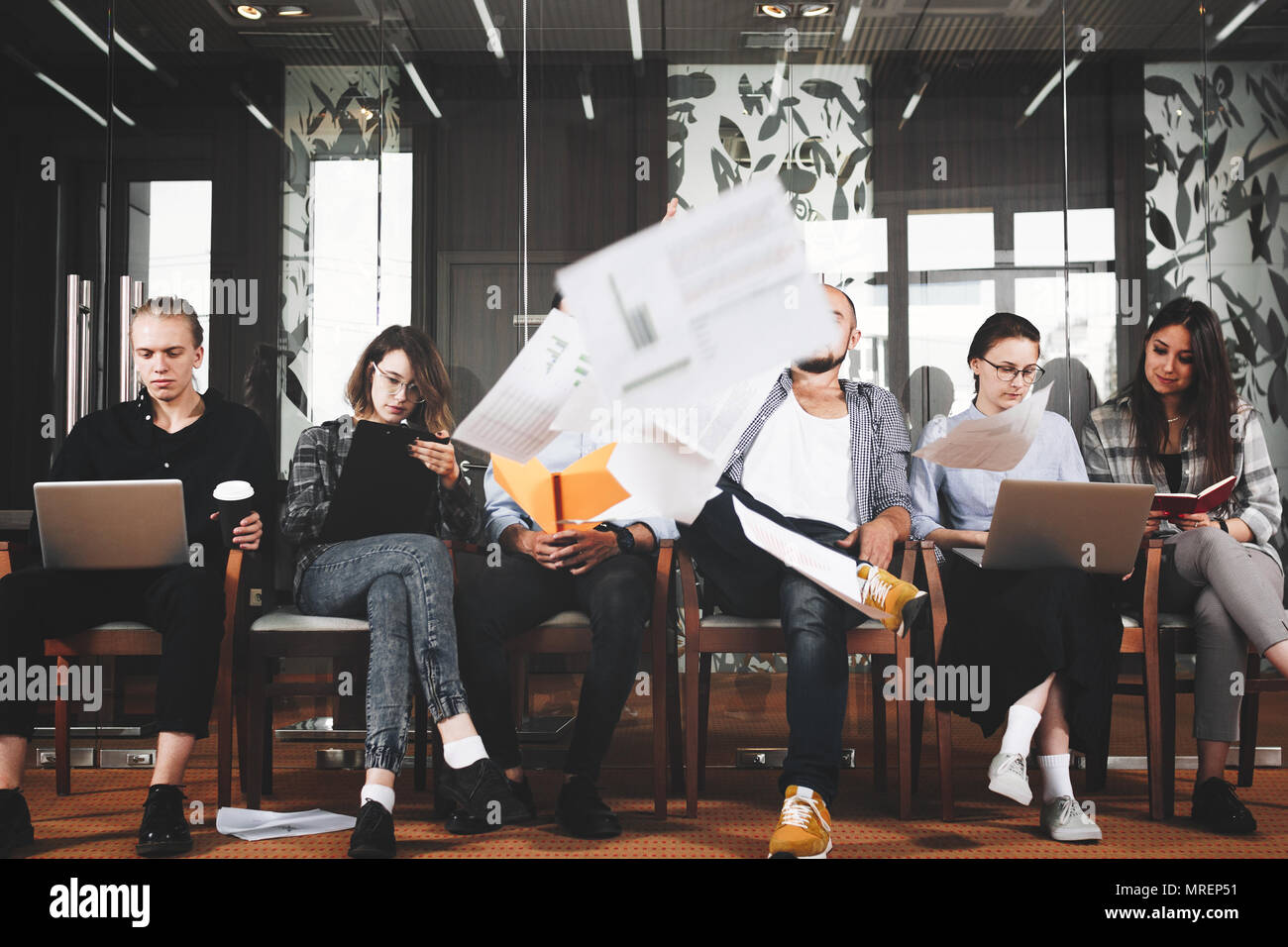 Creative happy hipsters decide to end their work days and begin of weekend through all documents. Creative team of happy hipsters - Stock Image