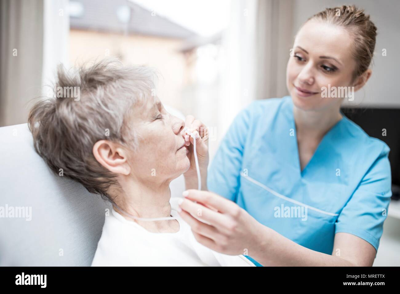 Care worker inserting nasal cannula in senior woman. Stock Photo