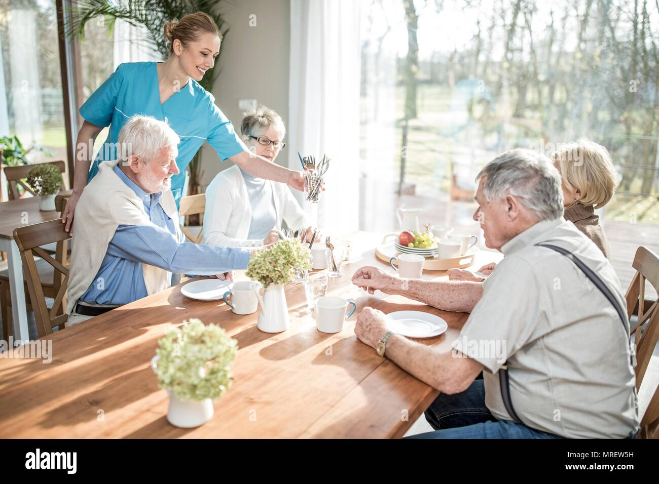 Female care worker serving senior adults at dinner table in care home. - Stock Image