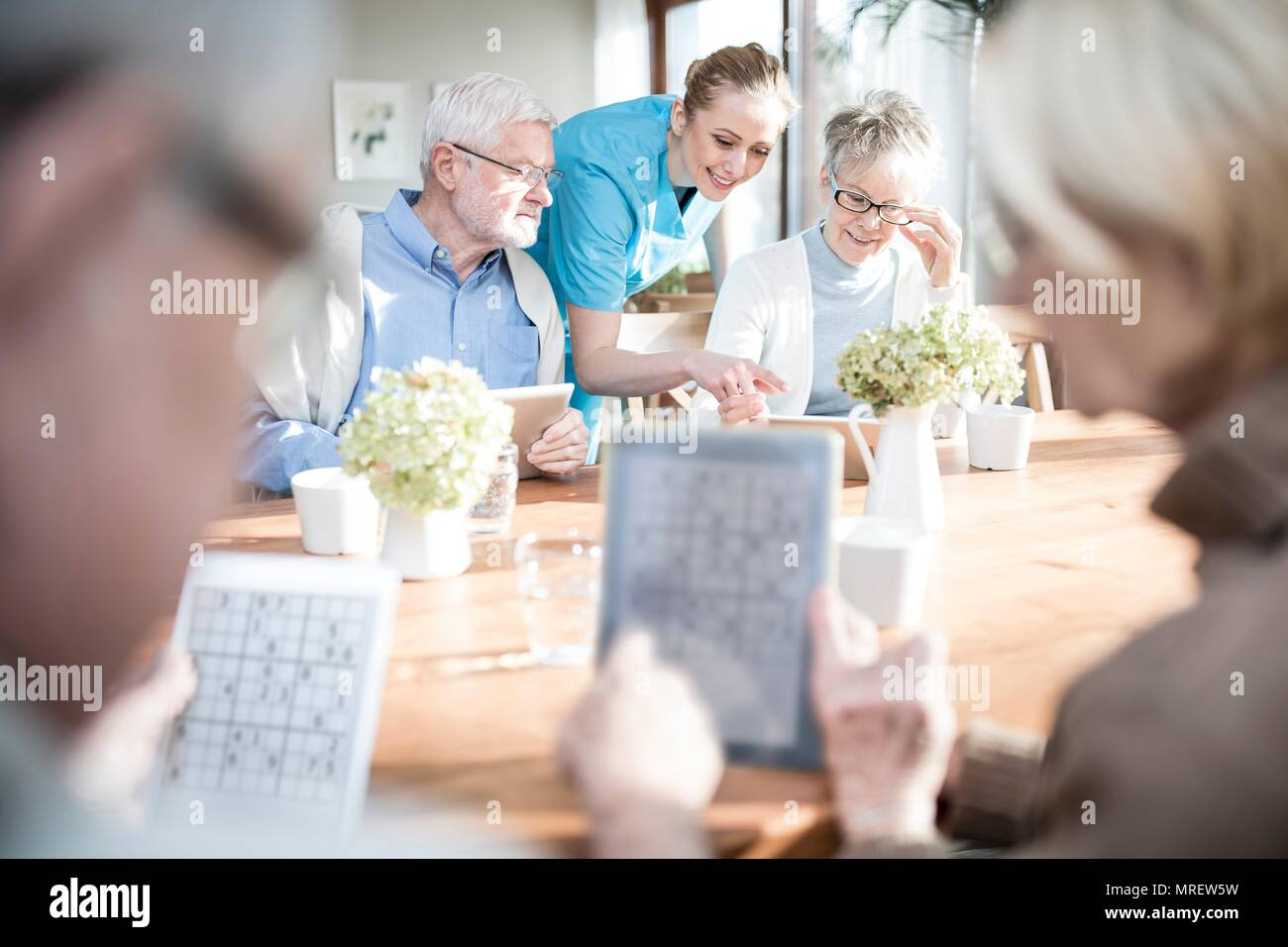 Senior adults playing games on digital tablets in care home. - Stock Image
