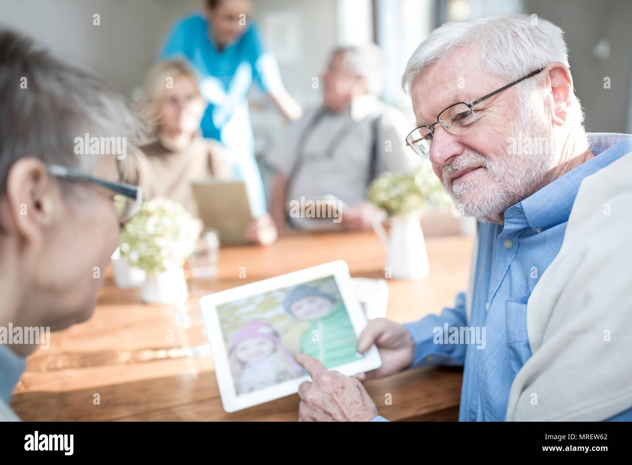 Senior adults looking at photos on digital tablet in care home. - Stock Image