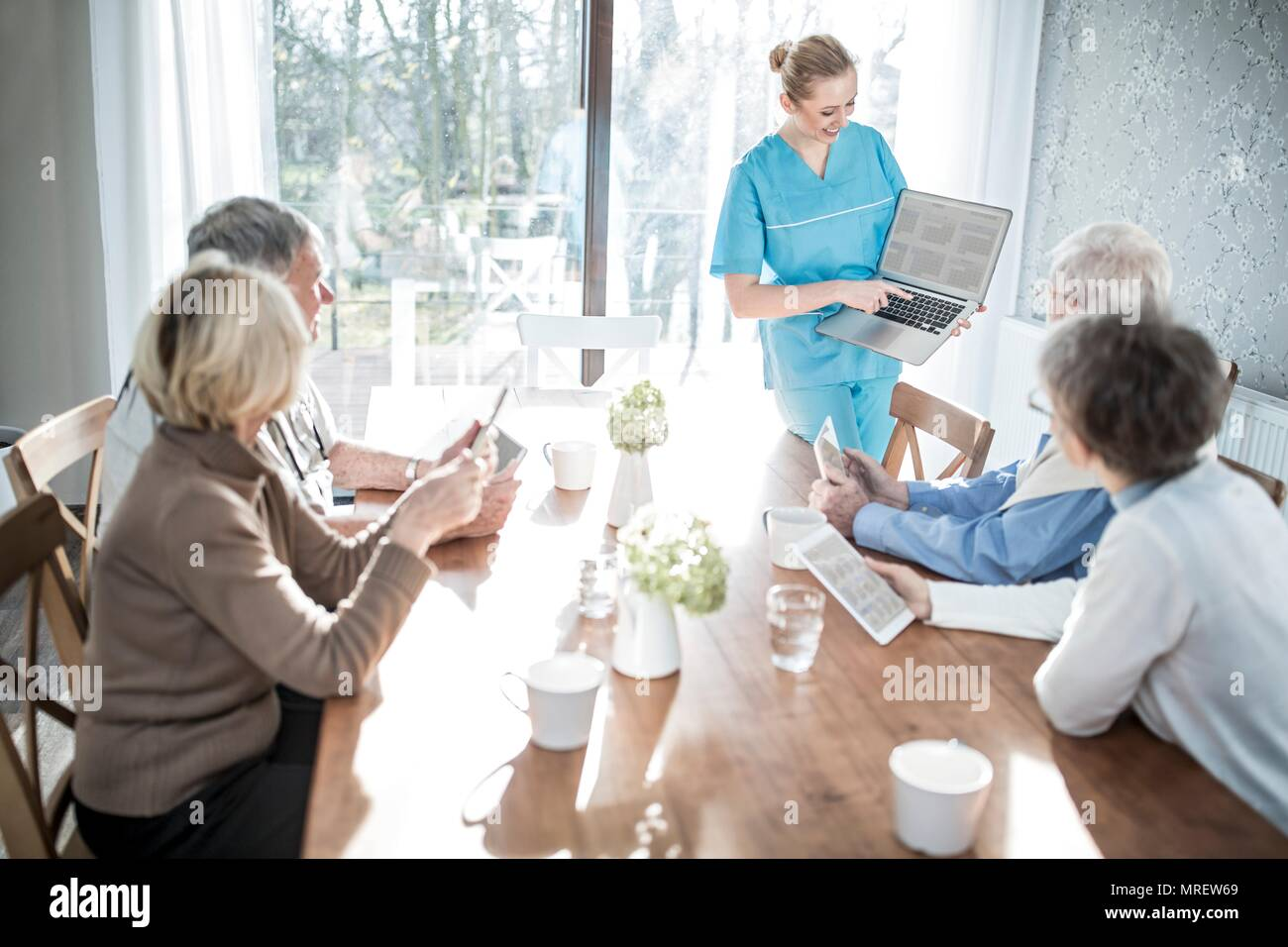 Care worker showing senior adults laptop in care home. - Stock Image