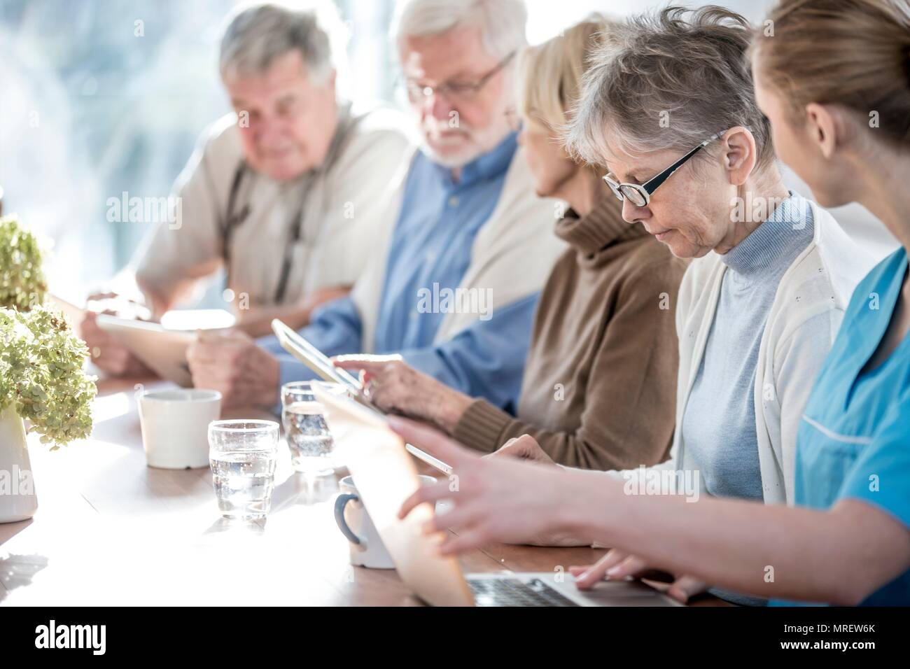 Senior adults in care home using digital tablets with care worker. - Stock Image