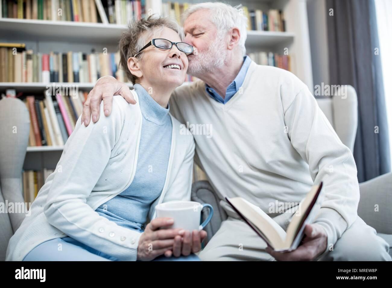 Senior man kissing woman on cheek with arm around her. - Stock Image