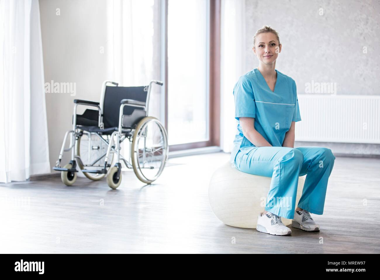 Young female physiotherapist sitting on Swiss ball with wheelchair in background. - Stock Image