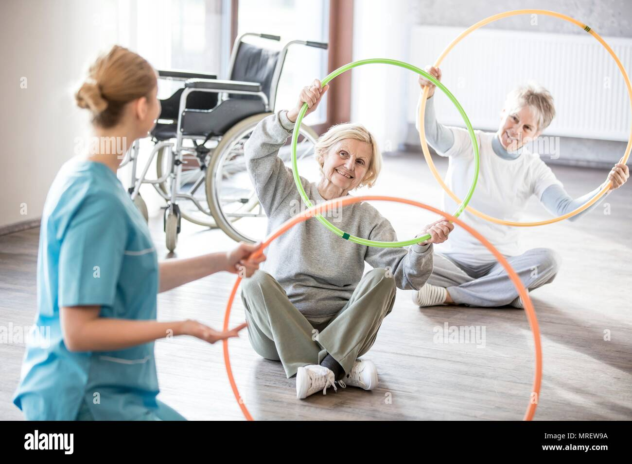 Physiotherapist with two senior women holding plastic hoops. - Stock Image