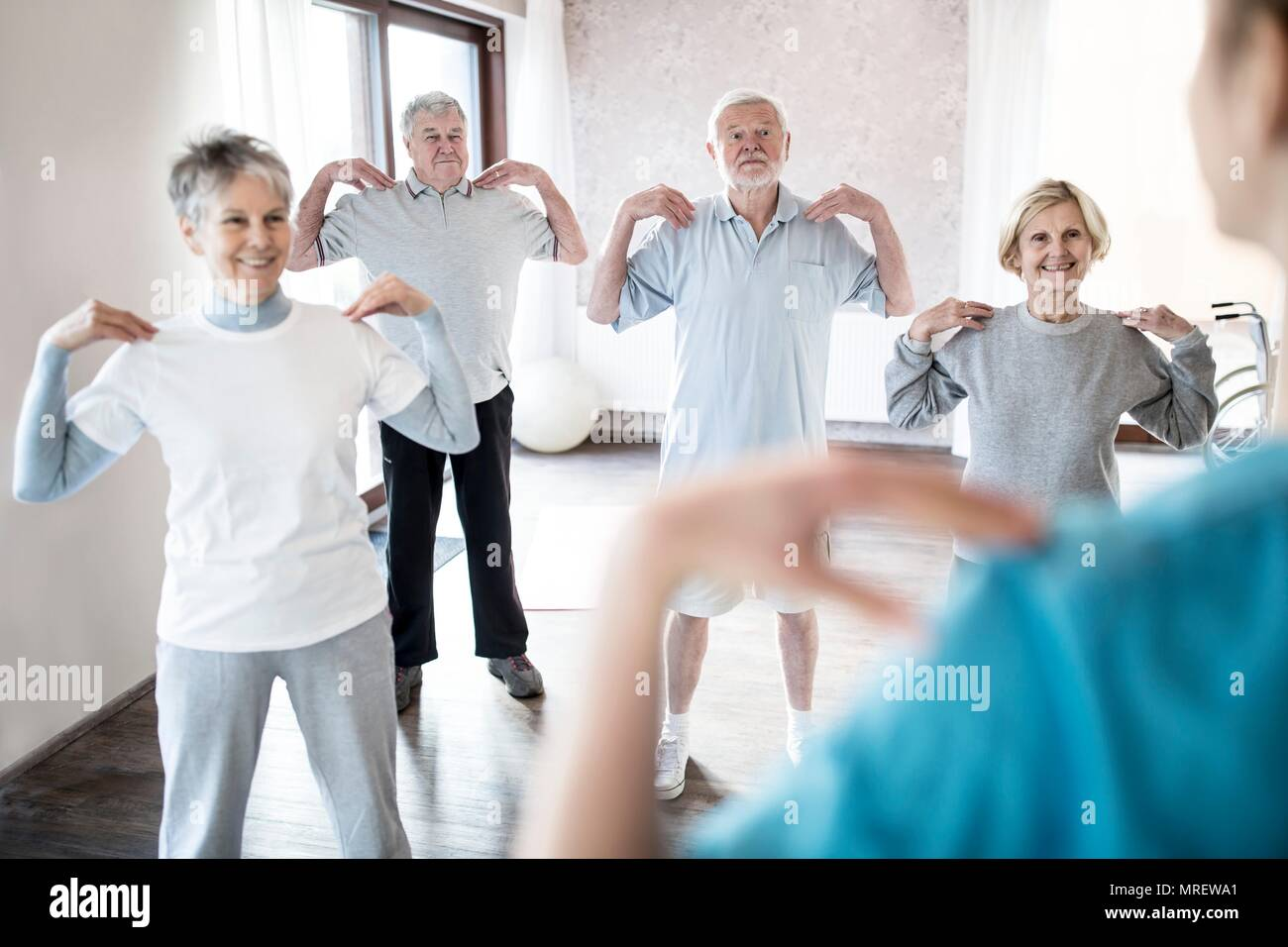 Senior adults doing exercise class. - Stock Image