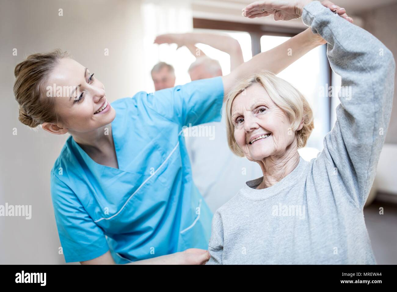 Senior woman stretching, physiotherapist helping. - Stock Image