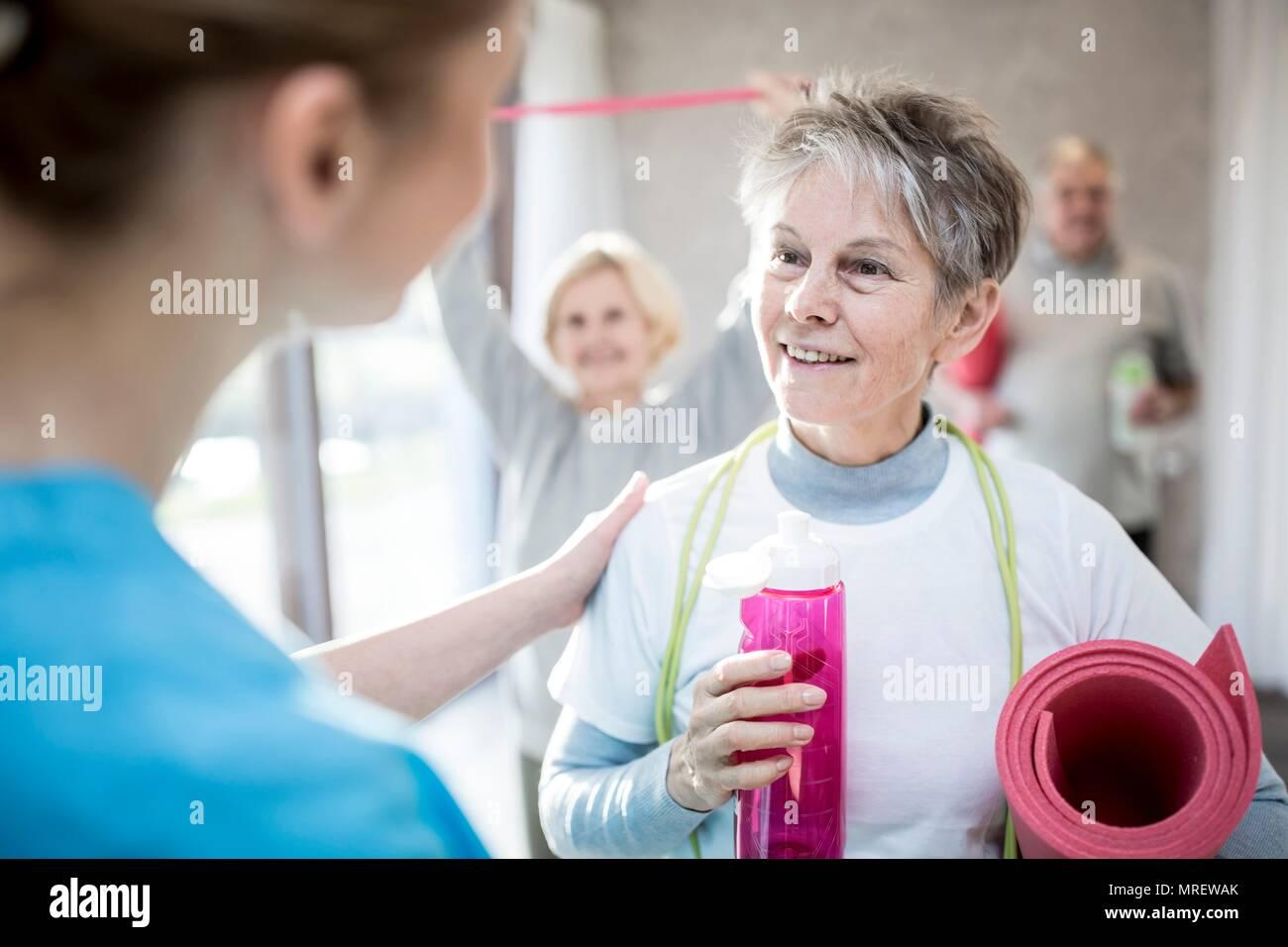 Senior woman talking to physiotherapist. - Stock Image