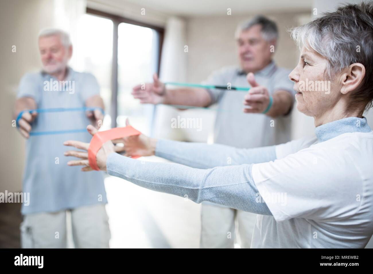 Senior adults using resistance bands in exercise class. - Stock Image