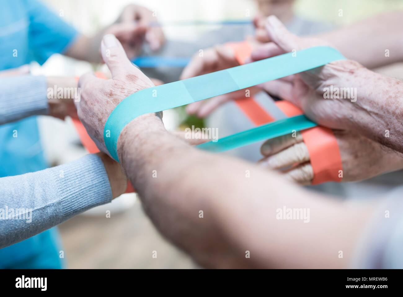 Close up of senior adults using resistance bands in exercise class. - Stock Image
