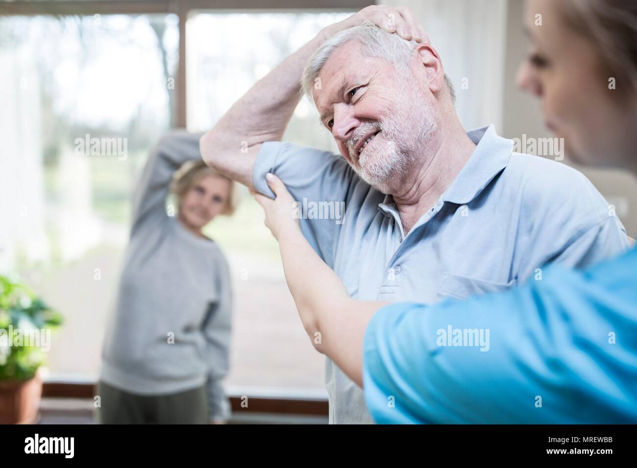 Senior man stretching, physiotherapist helping. - Stock Image