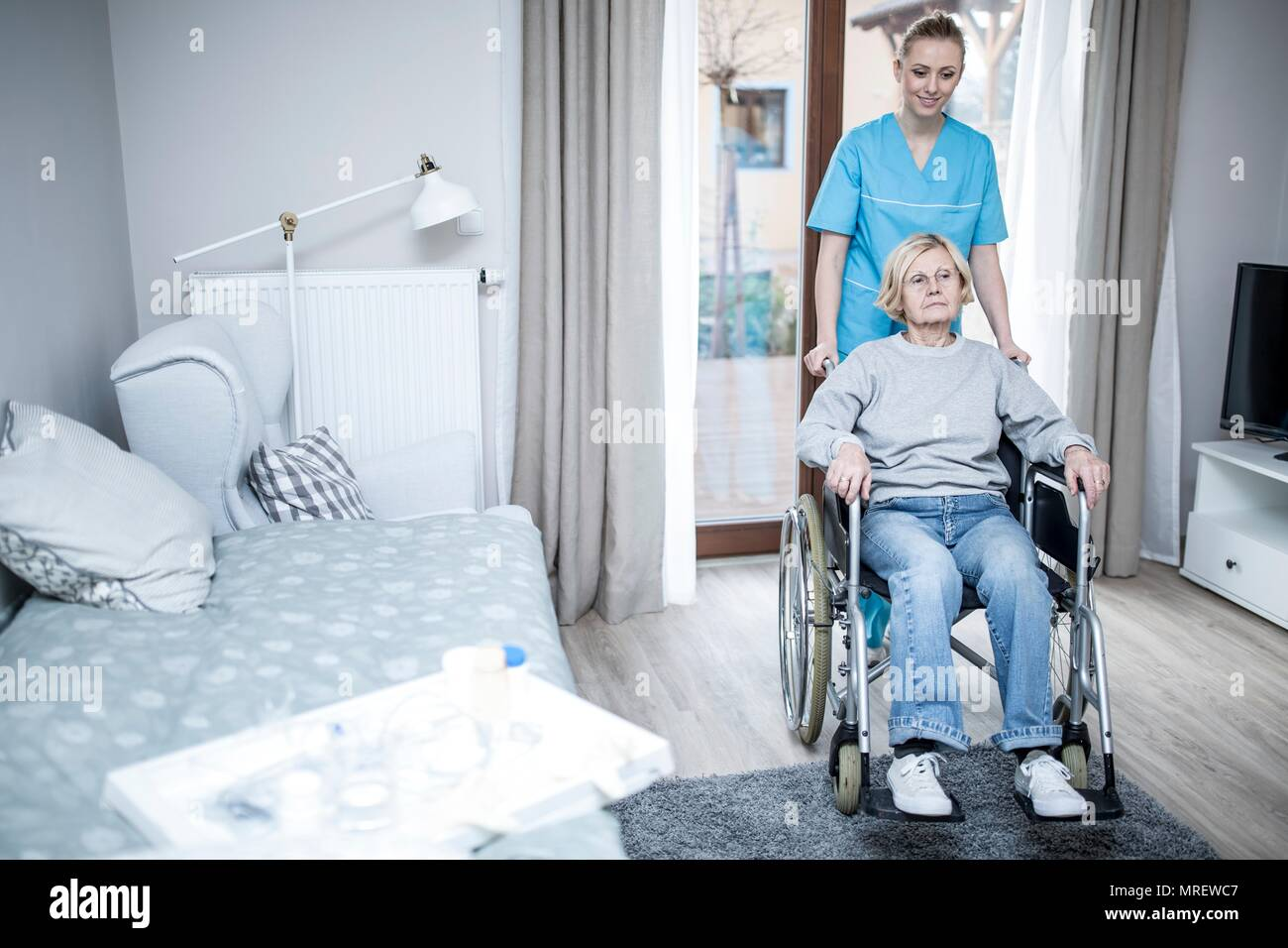 Senior woman in wheelchair with care worker in care home. - Stock Image