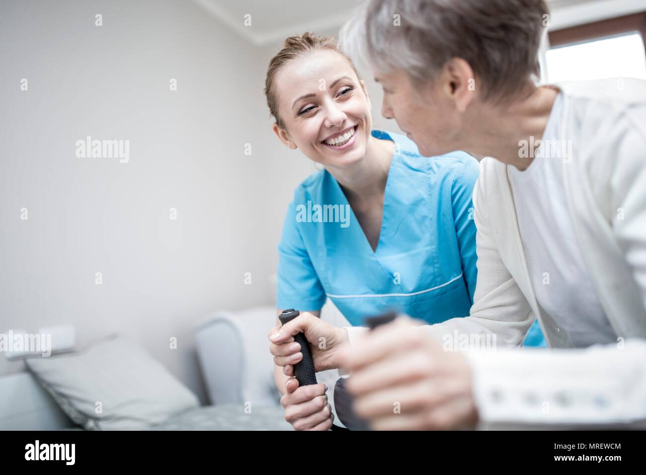 Senior woman using rollator with care worker assisting. - Stock Image