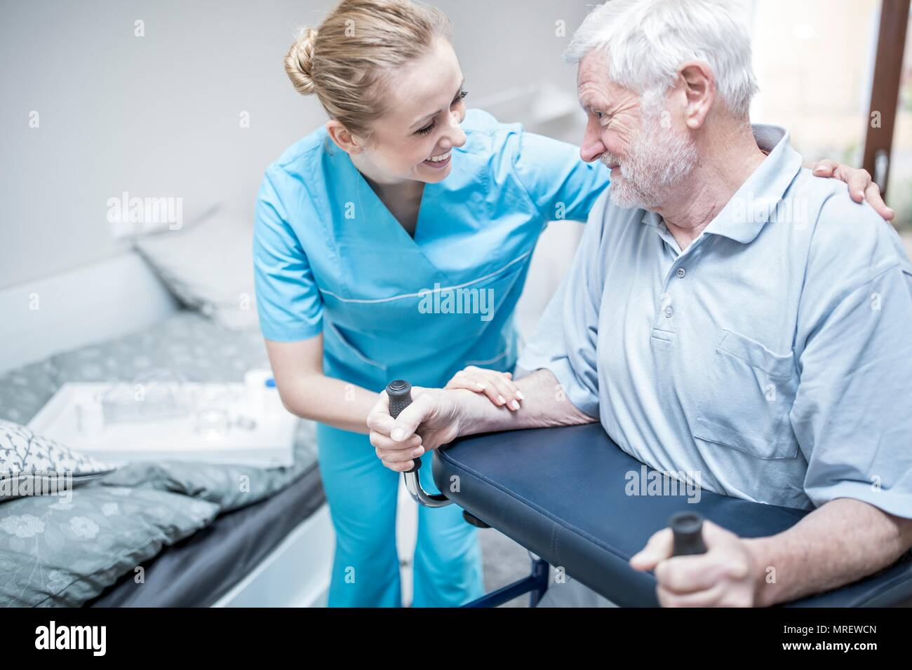 Senior man using rollator with care worker assisting. - Stock Image
