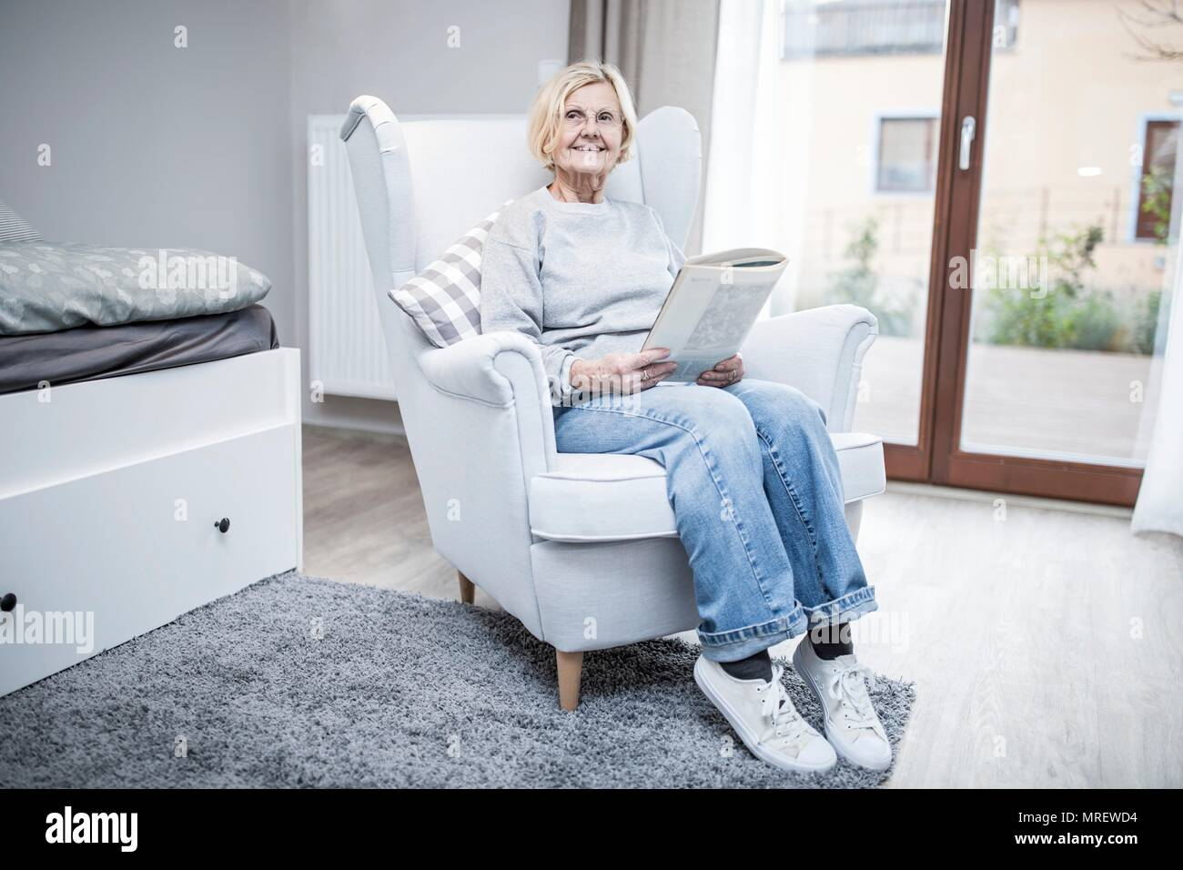 Senior woman sitting in armchair with magazine in care home. - Stock Image