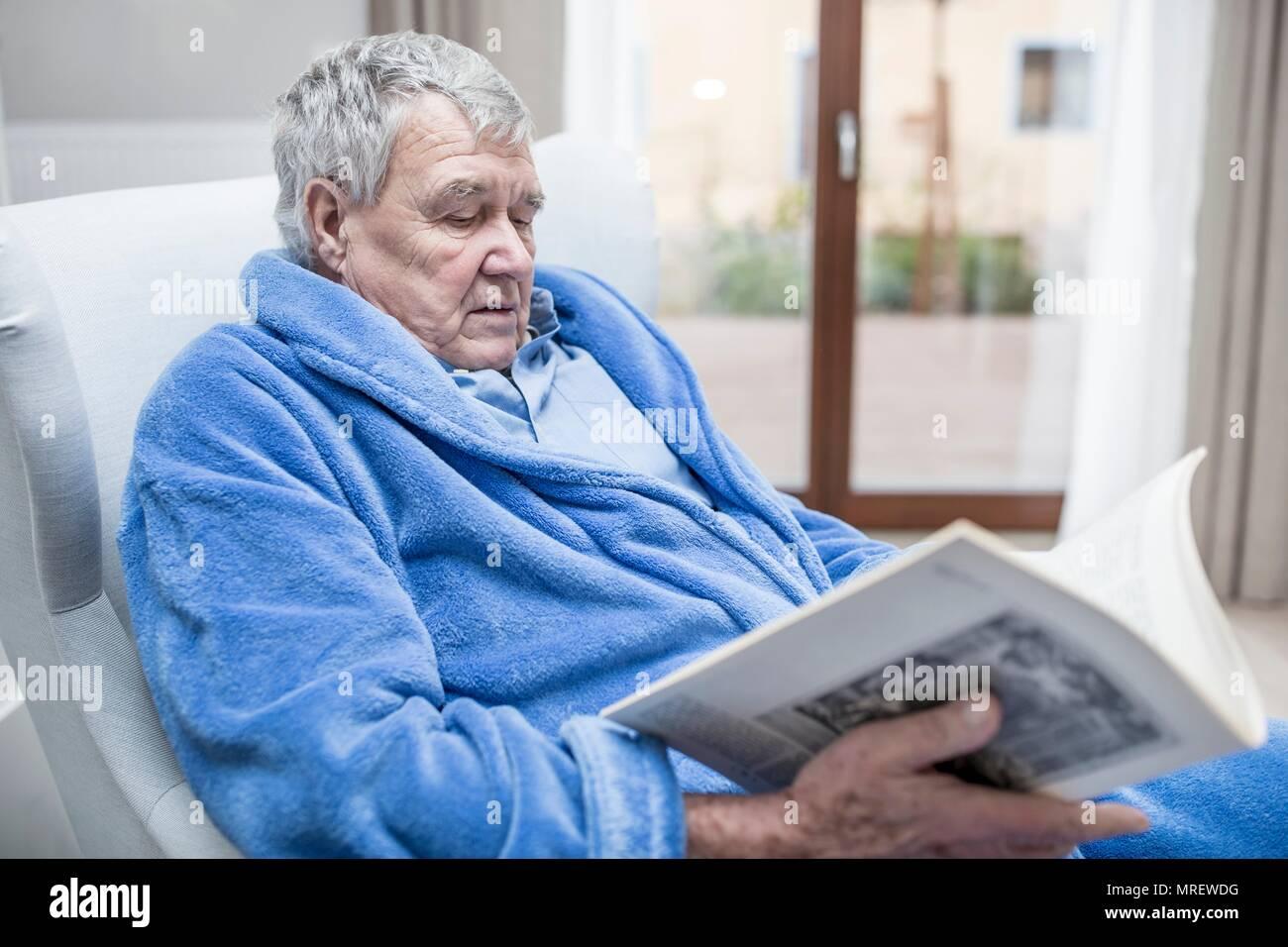 Senior man reading magazine in care home. - Stock Image