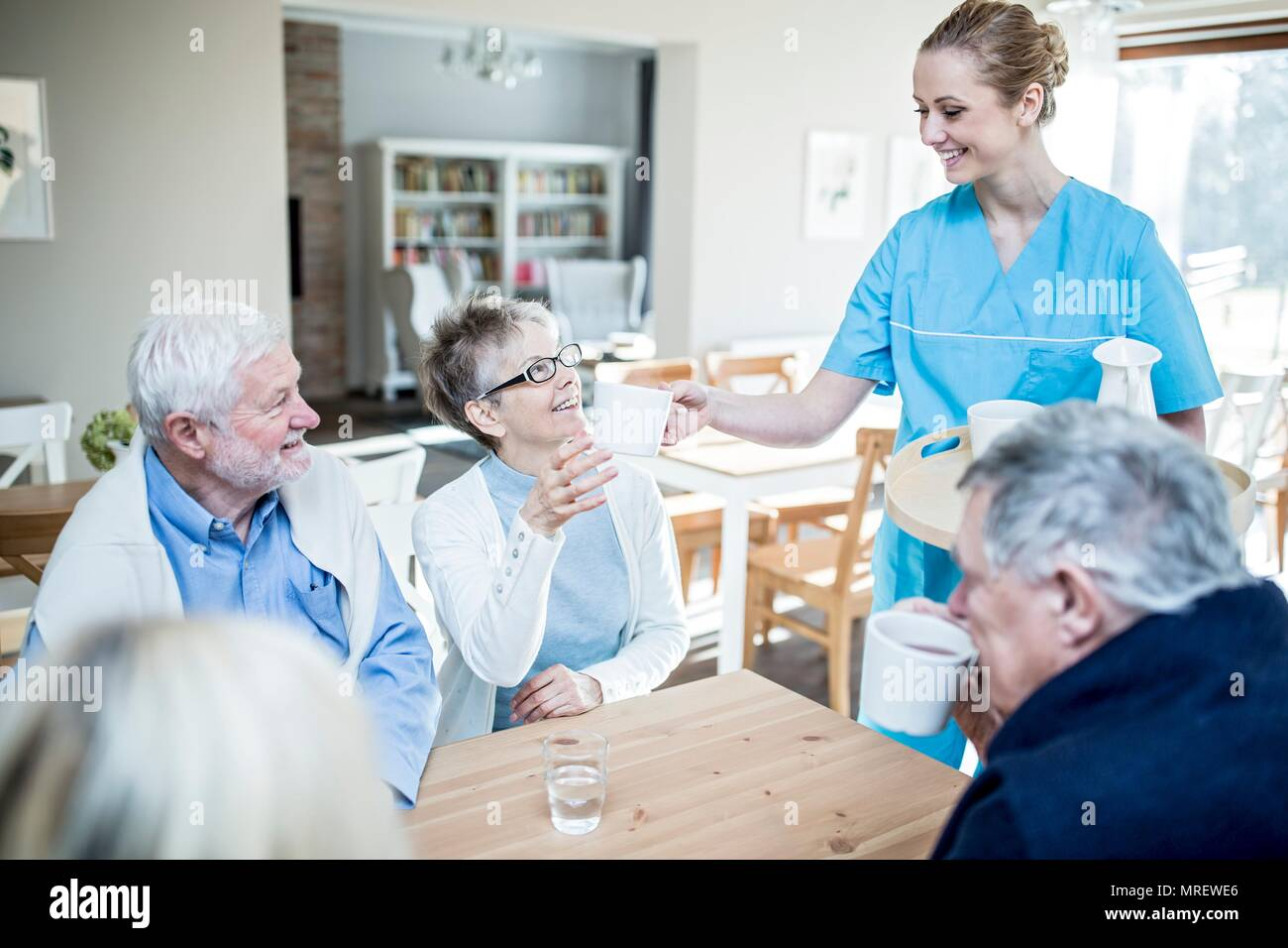 Care worker serving tea to senior woman in care home. - Stock Image